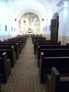 The chapel at Presidio La Bahia showing its wooden benches and bright white walls
